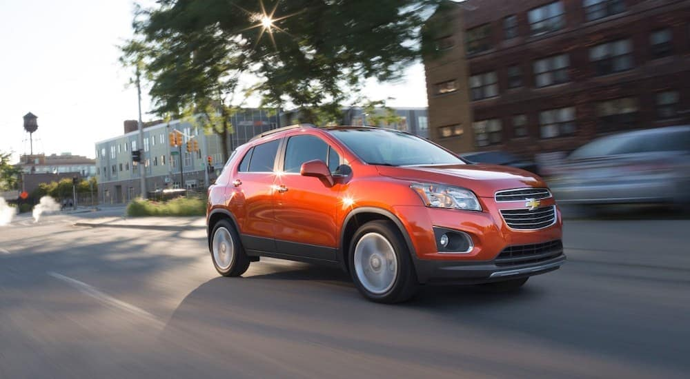 An orange 2016 Chevy Trax, a common choice among Certified Pre-Owned cars for sale in Cincinnati, OH, is driving down a city street.