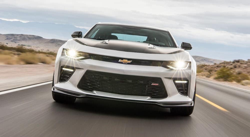 A white and black 2017 Chevy Camaro is driving toward the camera.