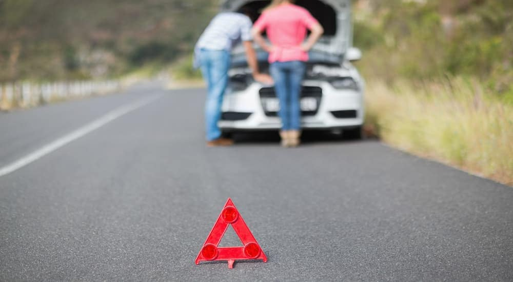 An orange warning marker is set up with a blurred couple and their broken car behind it.