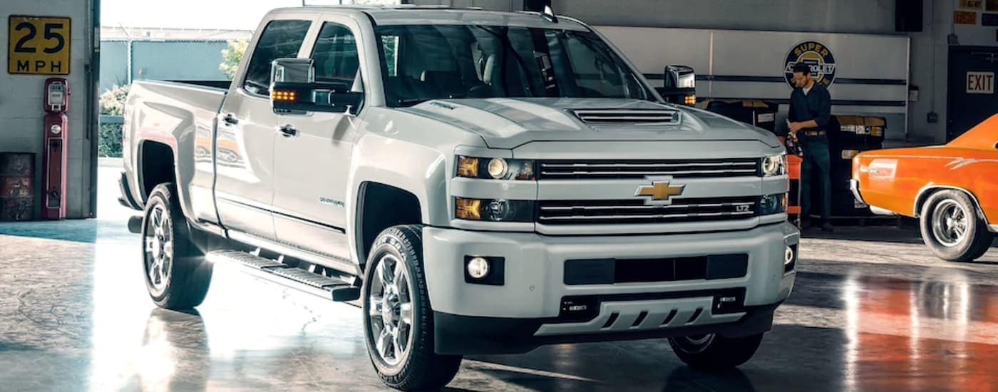 A white 2019 Chevy Silverado HD 2500 is parked in a large shop near Cincinnati, OH.