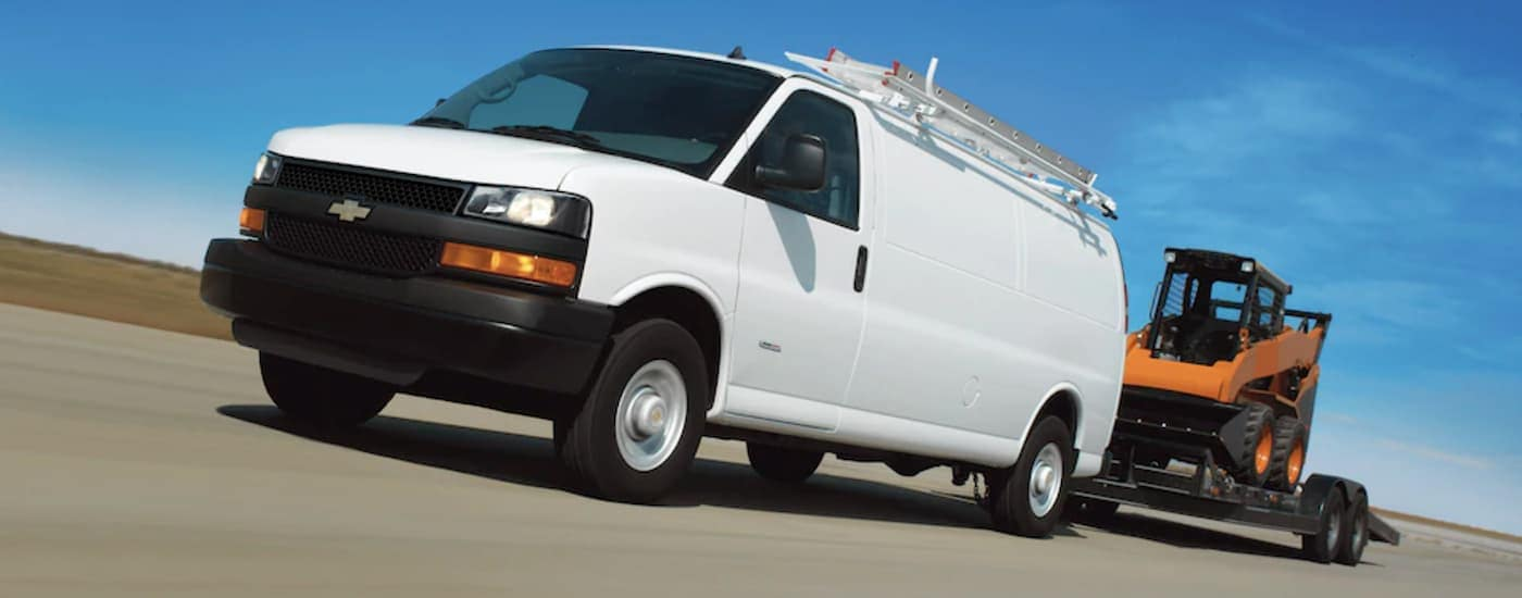 A white 2019 Express Cargo Van is towing a construction machine.