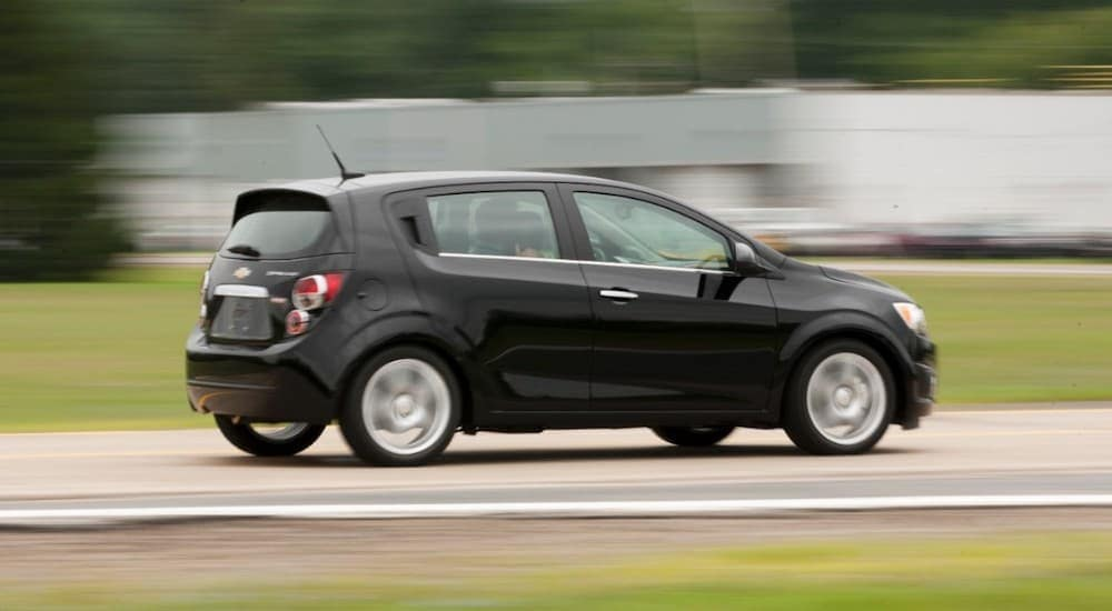 A black 2012 Chevy Sonic, popular among used cars under 10k for sale in Cincinnati, OH, is driving past a blurred white building.