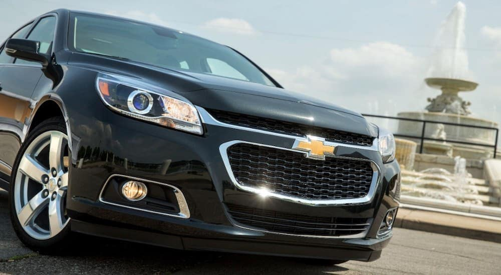 The front of a black 2014 Chevy Malibu is shown in front of a fountain.