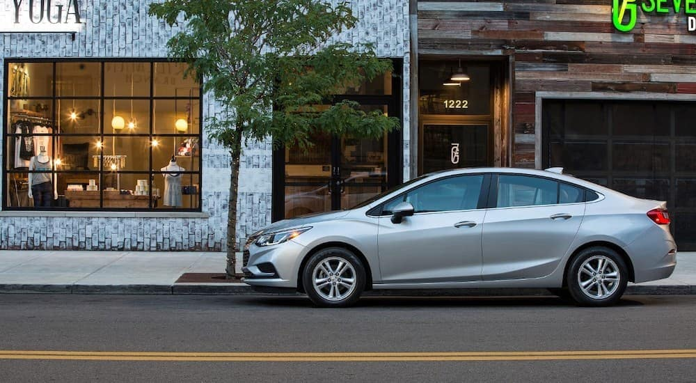A silver 2017 Chevy Cruze, popular among used cars for sale in Cincinnati, OH, is parked in front of shops.