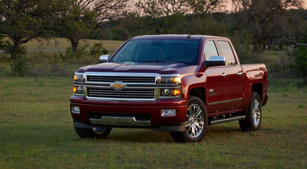 A red 2014 Chevy Silverado is parked in a grassy area.