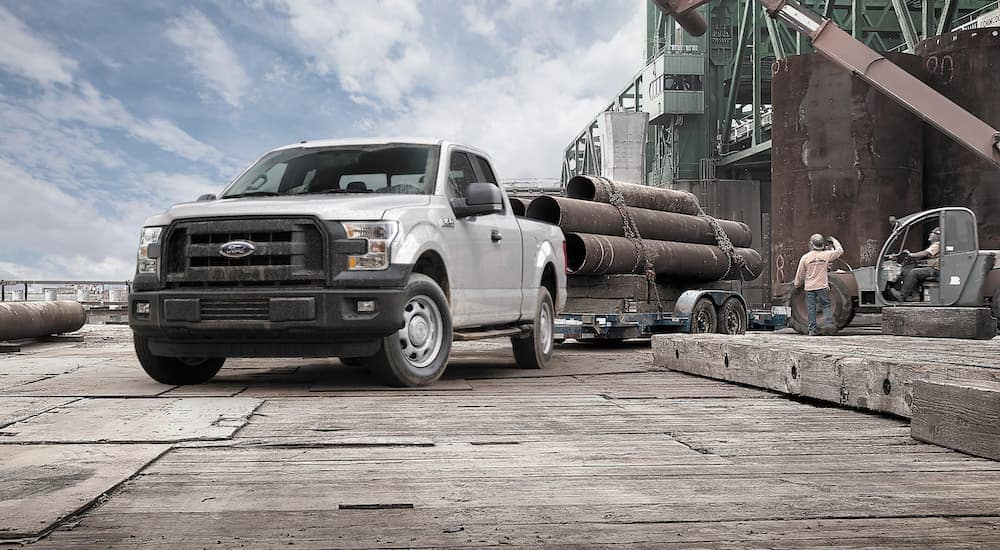 A white 2015 Ford F150 is towing a trailer loaded with pipe.