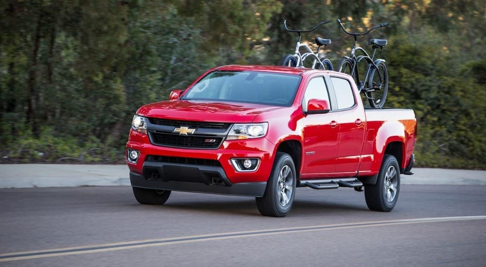 A red 2017 Chevy Colorado, popular among used trucks for sale in Cincinnati, is driving with bikes in the bed.