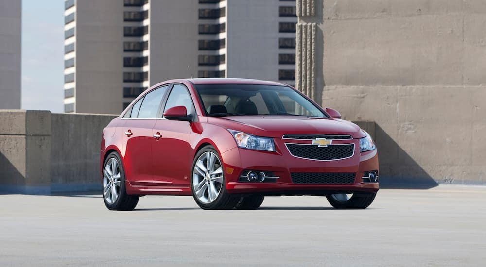 A red 2014 Chevy Cruze is parked on a top level parking garage.
