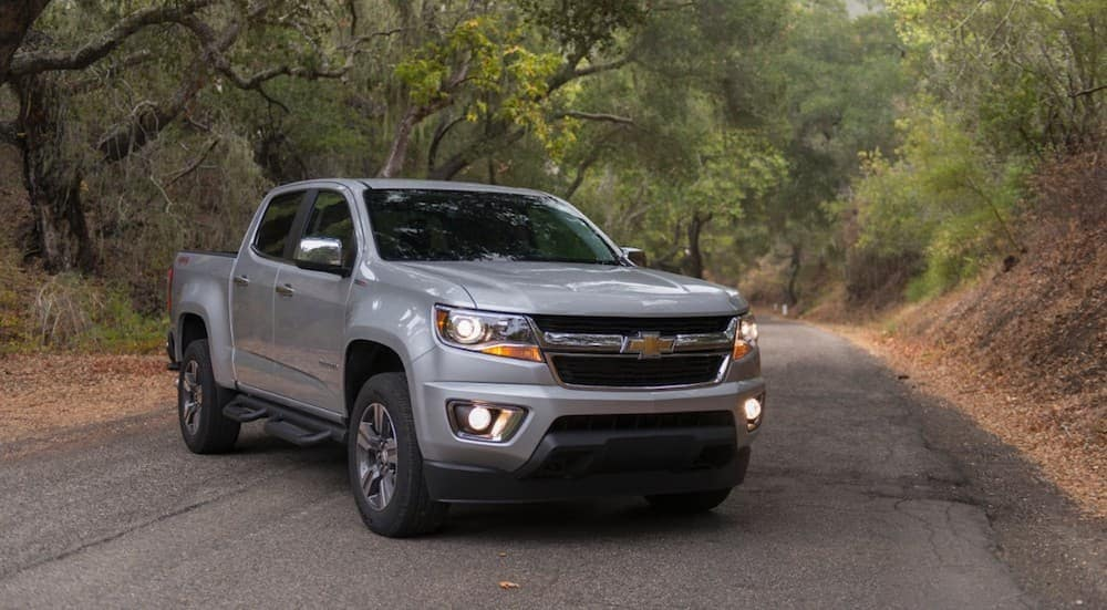 A silver 2016 Chevy Colorado, popular among used trucks for sale, is parked on a wooded road near Cincinnati, OH.