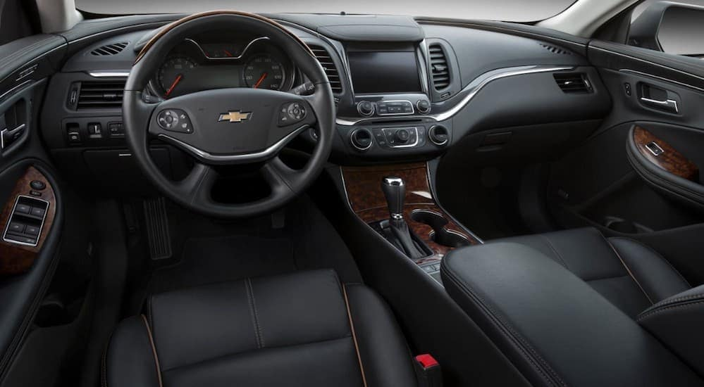The front black leather interior in a 2016 Chevy Impala is shown.