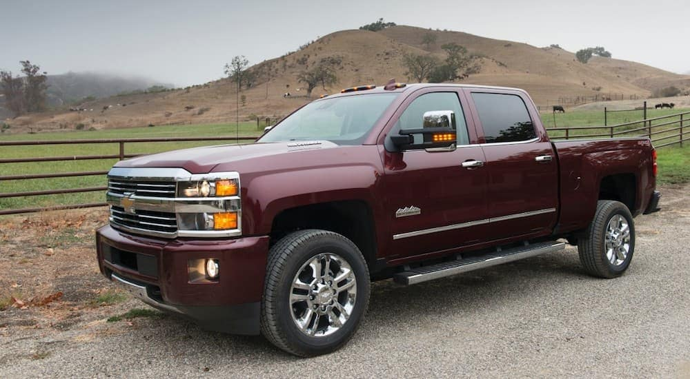 A burgundy 2016 Chevy Silverado 2500HD crew cab, popular among used trucks for sale in Cincinnati, OH, is parked near a farm.