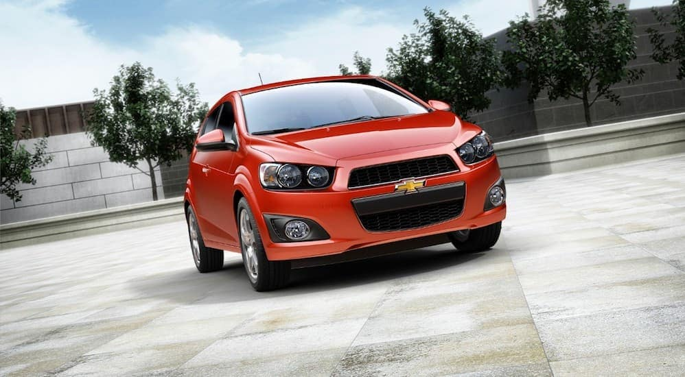 A red 2016 Chevy Sonic, popular among cars priced under $10k, is parked in a parking lot near Cincinnati, OH.