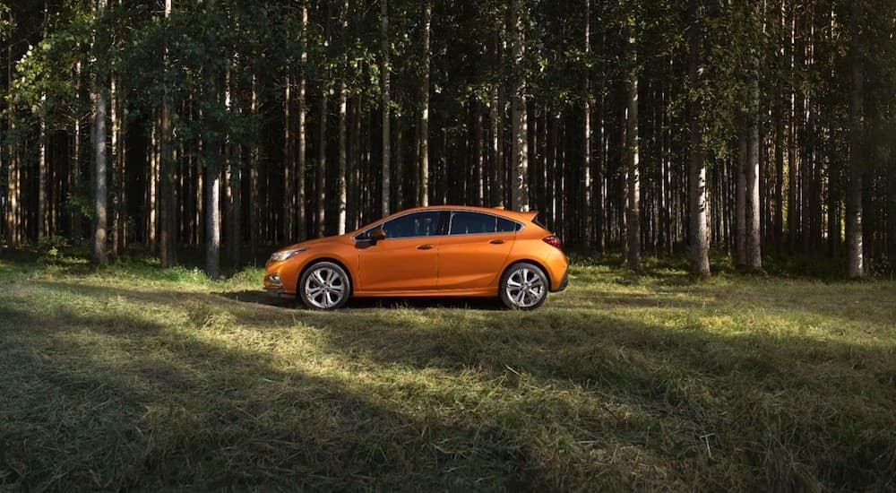 An orange 2017 Chevy Cruze, popular among used cars for sale, is parked on a wooded trail outside of Cincinnati, OH.