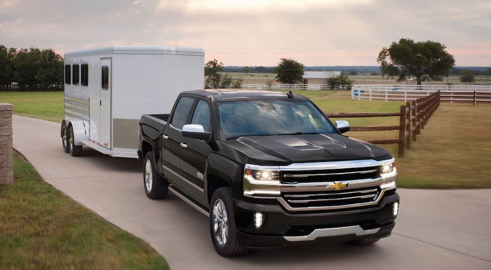 A black 2018 Chevy Silverado 1500, easy to find searching used trucks for sale neat Cincinnati, OH, is towing a trailer.