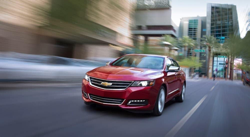 A red 2019 Chevy Impala is driving downtown.