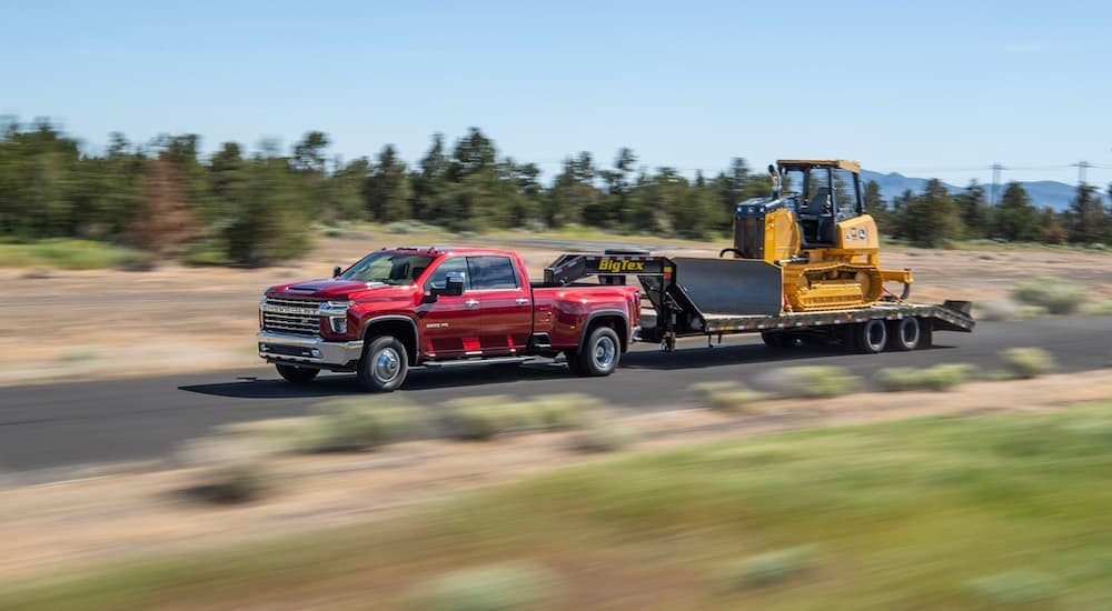 A red 2020 Chevy Silverado 3500HD, a favorite among Diesel Trucks For Sale, is driving on a road near Cincinnati, OH is towing heavy work equipment.