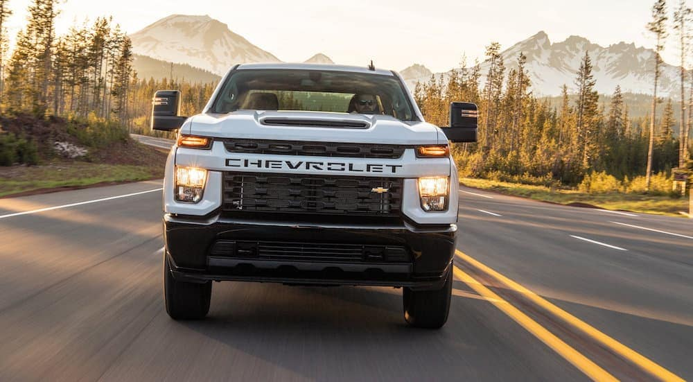 The front end of a 2020 Chevy Silverado 2500, popular among Diesel Trucks For Sale in Cincinnati, OH, is driving on a highway with mountains behind it.