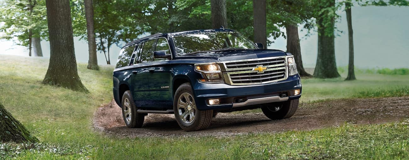 A blue 2020 Chevy Suburban LS is driving on a dirt path in the woods.