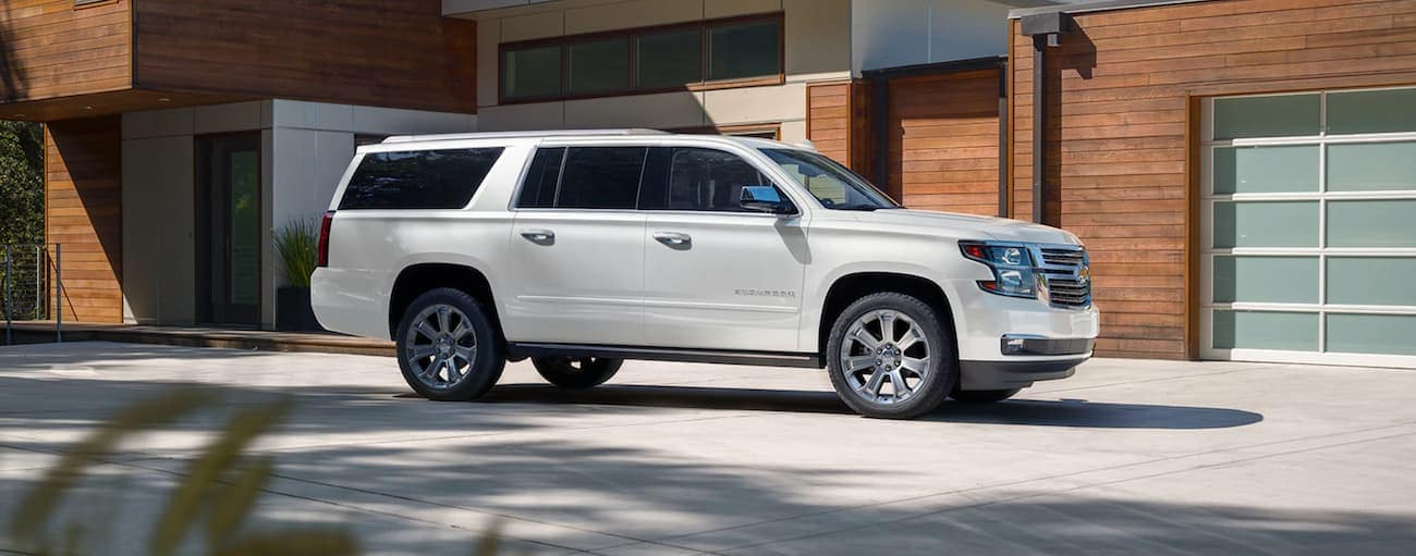 A white 2020 Chevy Suburban Premier is parked in front of a modern house near Cincinnati, OH.