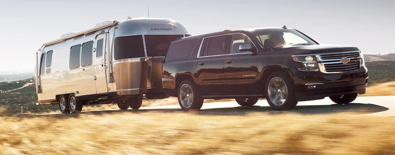 A black 2020 Chevy Suburban is towing an Airstream up a hill outside of Cincinnati, OH.