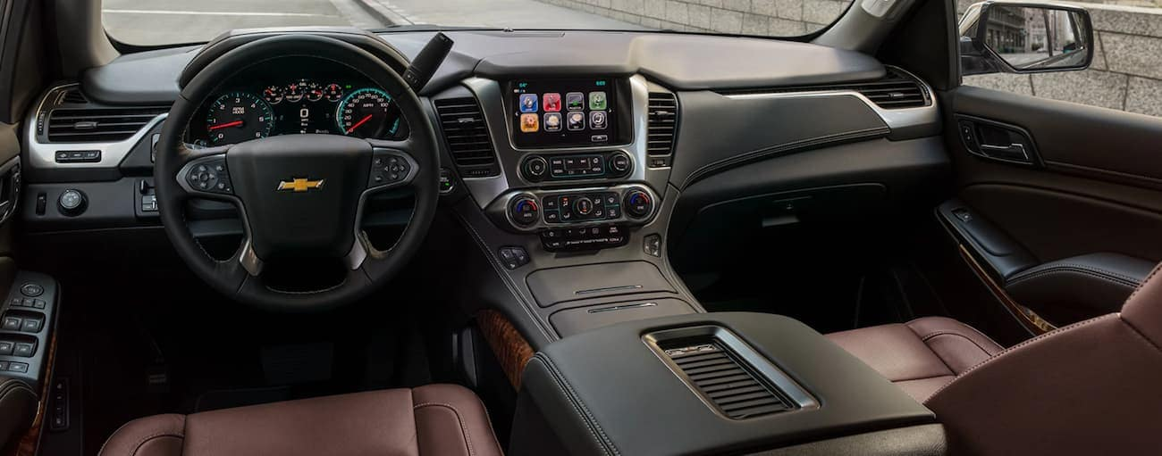 The black and burgundy leather interior of a 2020 Chevy Suburban is shown.