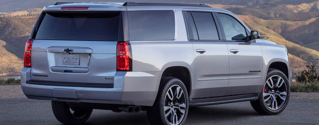 A silver 2020 Chevy Suburban is parked in front of mountains during sunset.