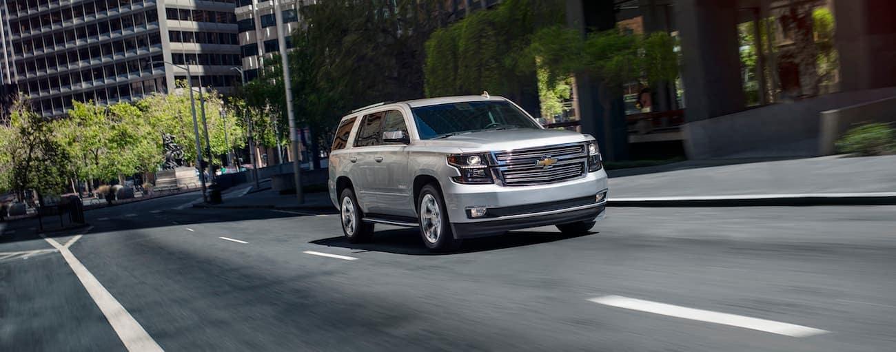 A silver 2020 Chevy Tahoe is driving through a city near Cincinnati, OH.