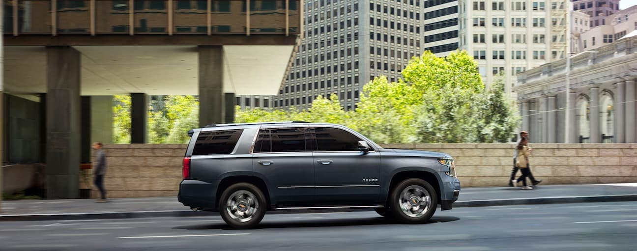 A grey 2020 Chevy Tahoe is shown from the side driving through a city.