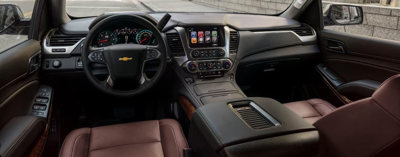 The black and burgundy leather interior of a 2020 Chevy Tahoe is shown.