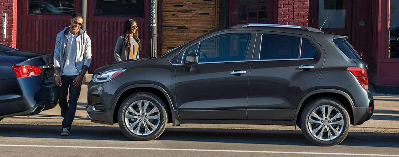 A smiling couple is walking to their dark grey 2020 Chevy Trax.