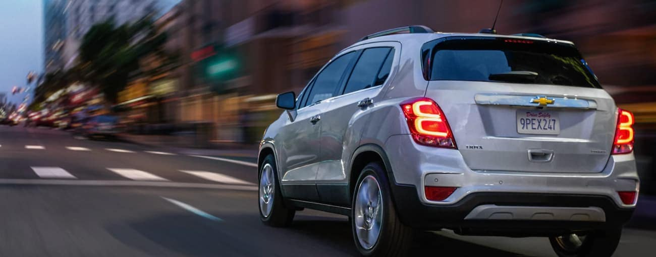 A silver 2020 Chevy Trax is driving through a city near Cincinnati, OH at night.