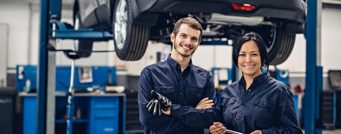Two technicians are standing in front of a car on a lift smiling.