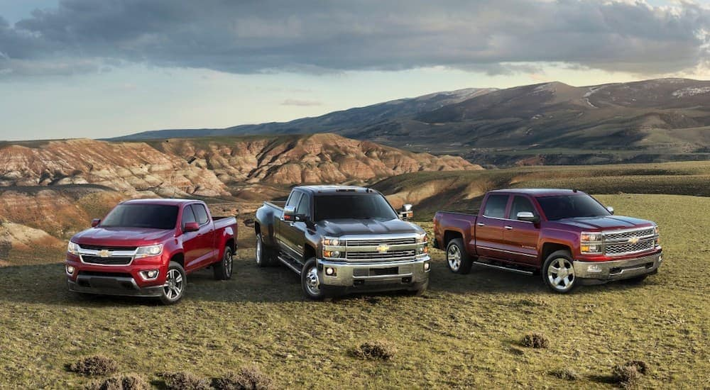 A 2015 Chevy Colorado, SilveradoHD, and Silverado 1500, popular among used cars for sale, are parked with mountains in the distance.