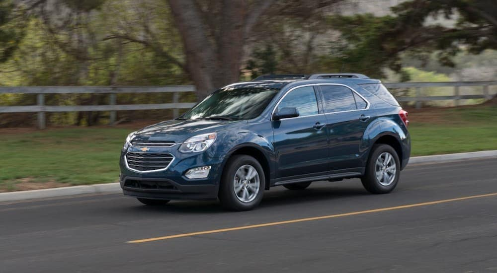 A blue 2016 Chevy Equinox is driving past a fence near Cincinnati, OH.