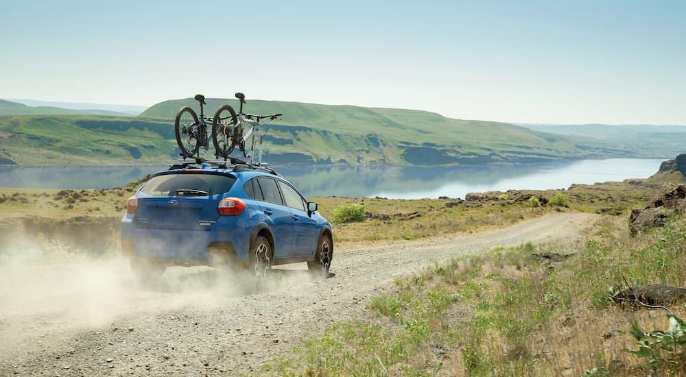 A blue 2017 Subaru Crosstrek is driving on a dirt road with bikes on top.