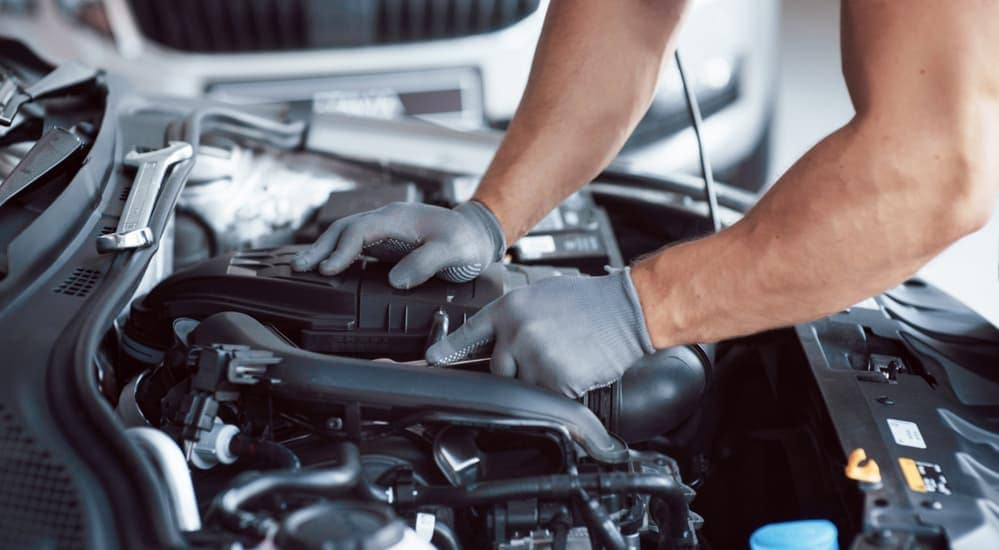 A mechanic's hands are reaching into an engine bay to doing a quick lube in Cincinnati, OH