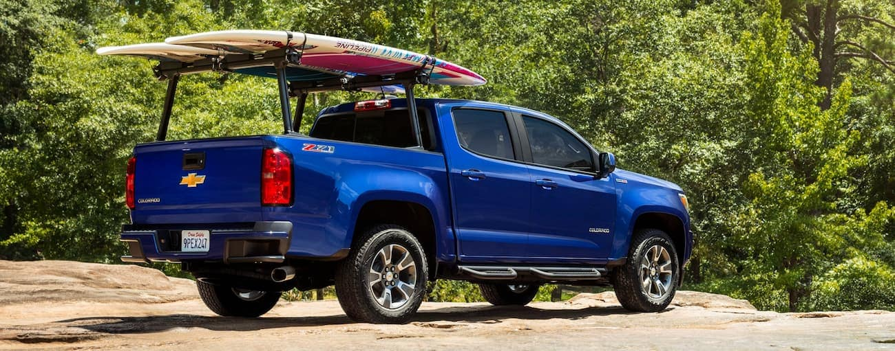 A blue 2019 Chevy Colorado with paddle boards on a bed rack is parked off-road outside Cincinnati, OH.
