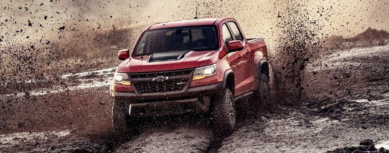 A red 2019 Chevy Colorado ZR2, which wins when comparing the 2019 Chevy Colorado vs 2019 Toyota Tacoma, is driving in the mud.
