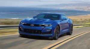 A blue 2020 Chevy Camaro SS is driving past the ocean.