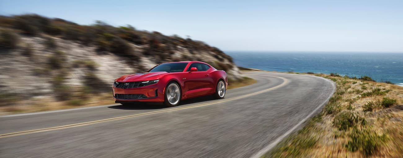 A red 2020 Chevy Camaro is driving past the ocean around a corner.