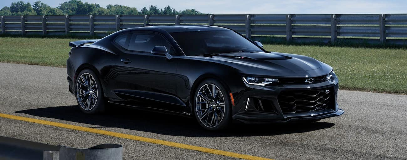 A black 2020 Chevy Camaro ZL1 is parked on a racetrack.