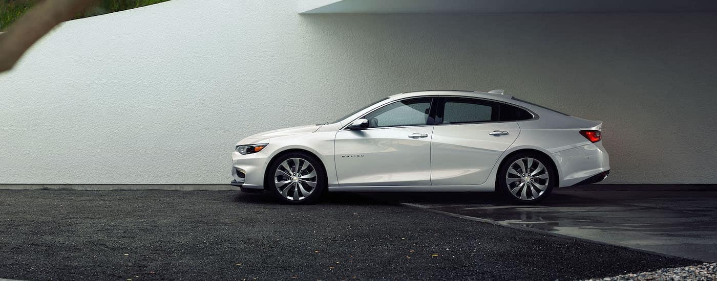 A white 2016 Chevy Malibu, popular among used cars in Dayton, Ohio, is parked in front of a white wall.