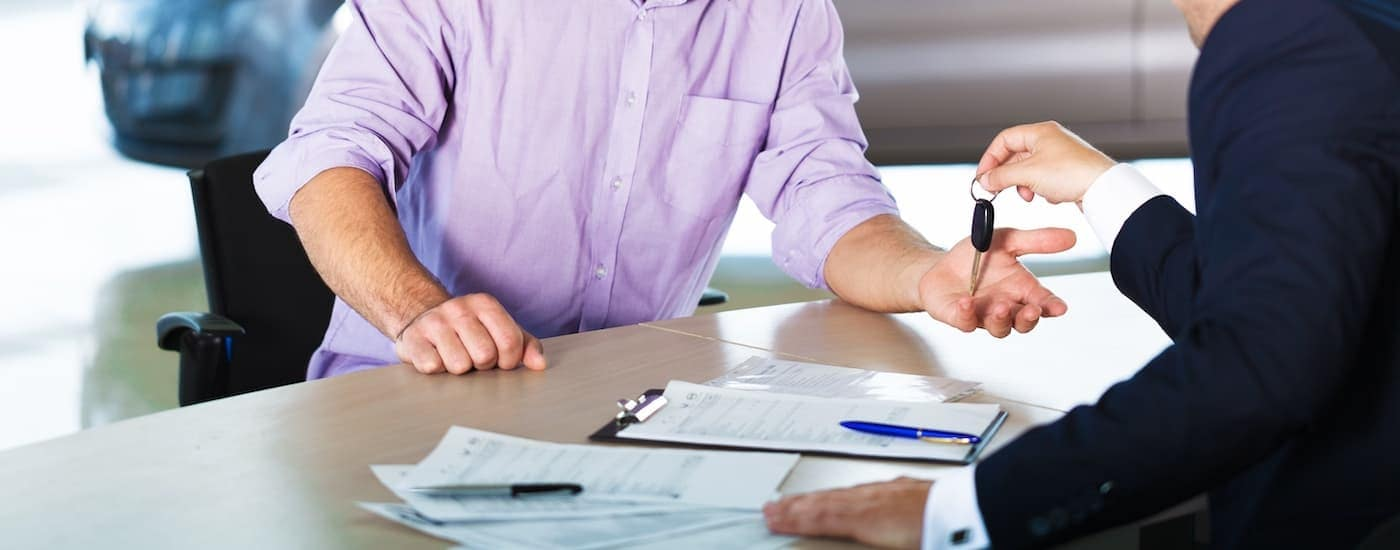 A salesman is handing keys to a buyer with paperwork on the desk.