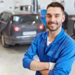 A mechanic is in a garage smiling.