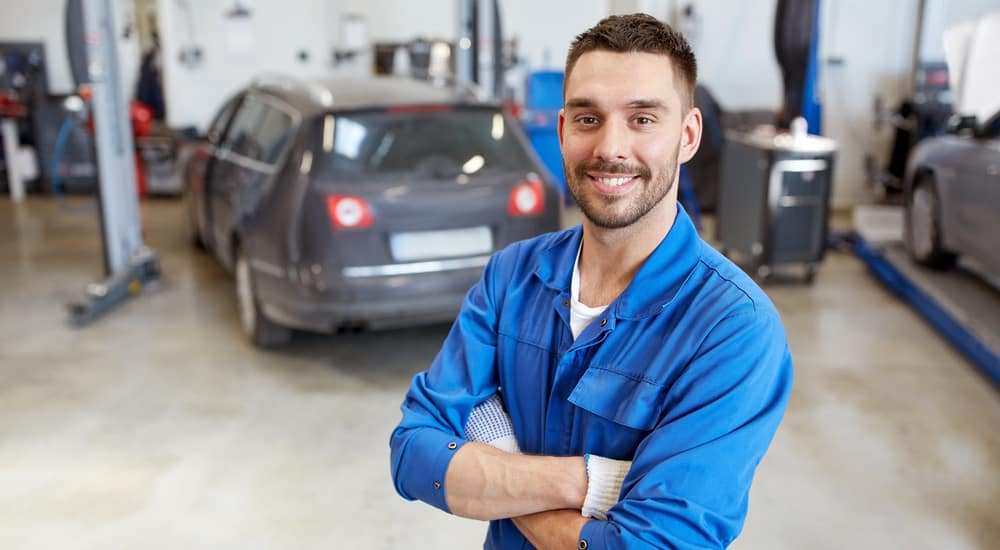 A mechanic, who you'll when searching car service near me, is in a garage smiling.
