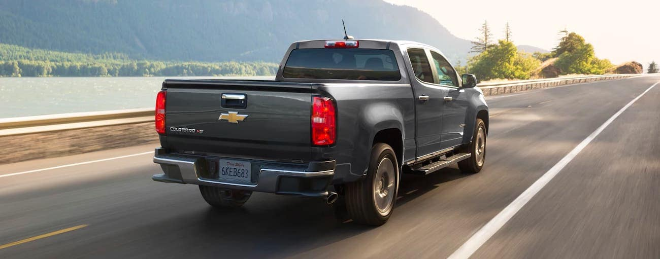 A gray 2020 Chevy Colorado Base is driving on a highway, facing away.