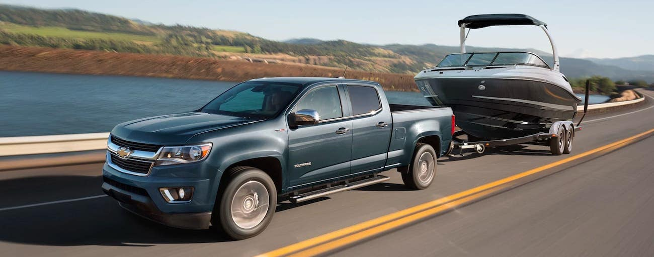 A gray 2020 Chevy Colorado LT is towing a boat past a lake.