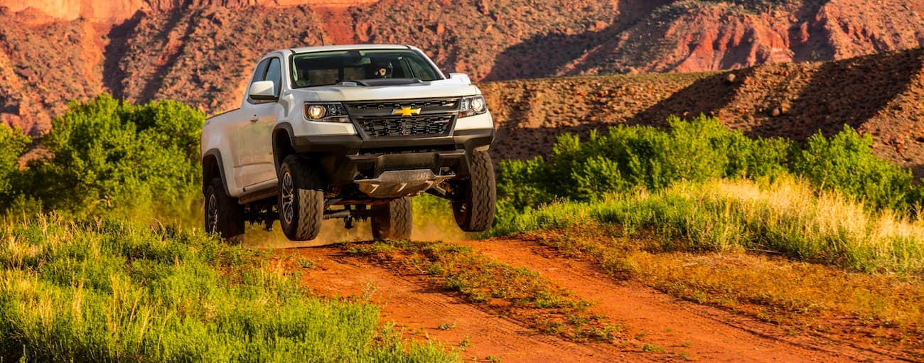 A white 2020 Chevy Colorado ZR2 is driving up a dirt road hill while in the air.