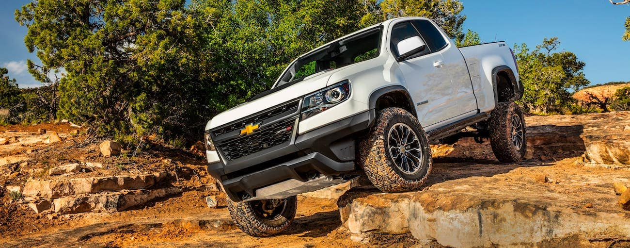A white 2020 Chevy Colorado ZR2 is crawling over rocks.