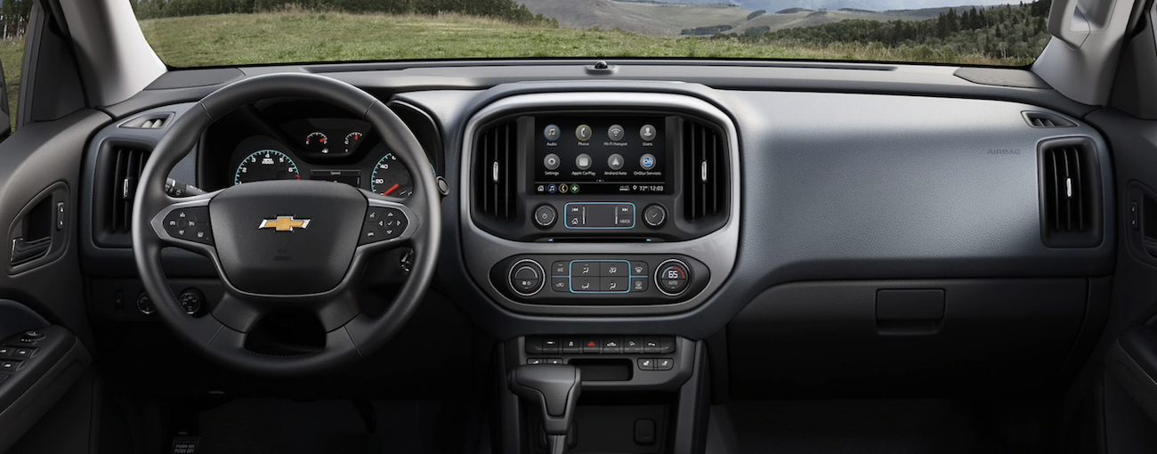 A close up of the front black leather interior of a 2020 Chevy Colorado with an infotainment system is shown.